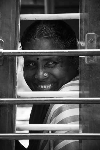 Smiling woman looking through window of bus