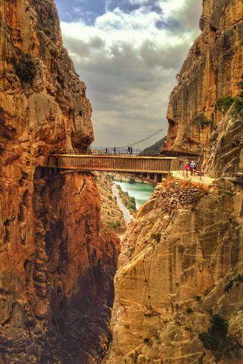 People on footbridge amidst rocky mountains