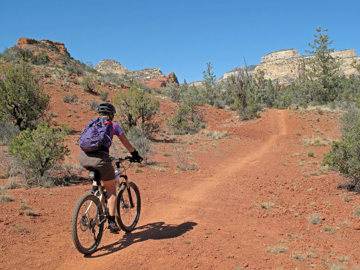 Woman riding bicycle on dirt road against sky