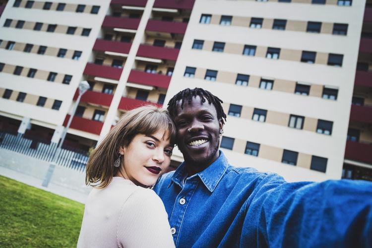 Portrait of happy friends smiling against building