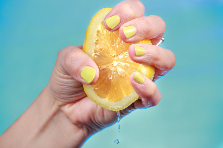 Cropped image of hand squeezing fruit against blue sky