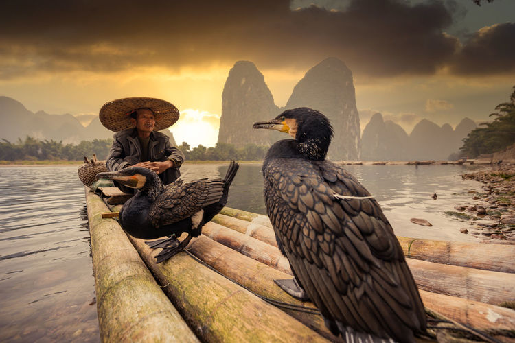 Man wearing hat sitting on raft with bird against mountains and sky