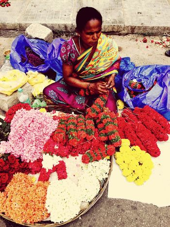Making floral garlands for the Gods. Streetwise flower vendor at Bangalore, India Streetphotography Flower Vendor Bangalore India IPhoneography