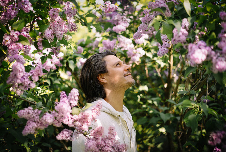 Portrait of smiling man standing by pink lilac flowers