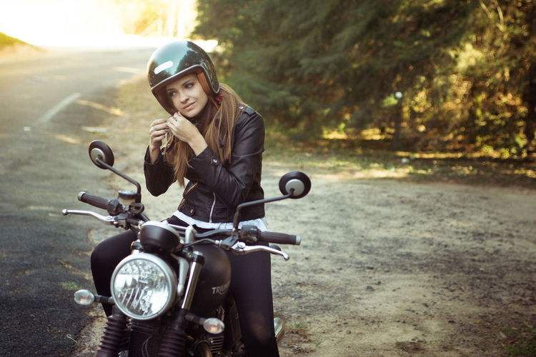 Young woman on motorcycle on road