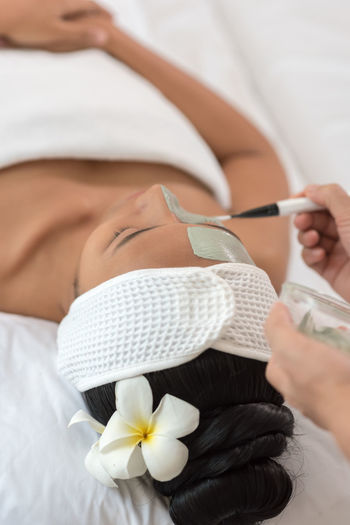Cropped hands of beautician applying facial mask on woman face at spa