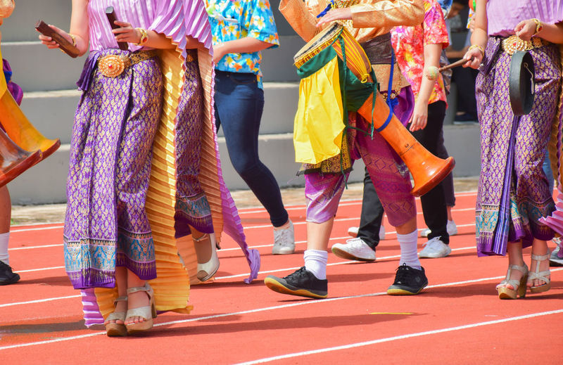 Low section of people in traditional clothing walking on running track