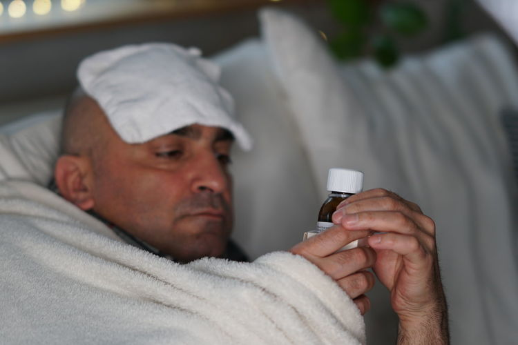 Sick man lying in the bed Medicine Cold And Flu Cough Disease Dosage Fever Illness Lying In Bed Medical Selective Focus Sick Man Sickness Sore Throat  Syrup Temperature Vaccinated Vaccination Vaccine