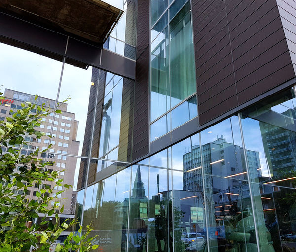 Low angle view of buildings seen through glass window