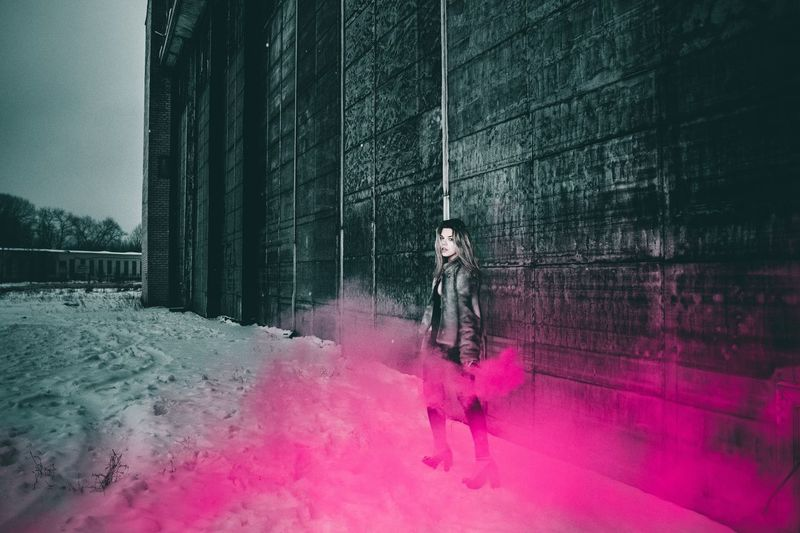 Portrait Of Woman Holding Distress Flare While Standing By Building During Winter