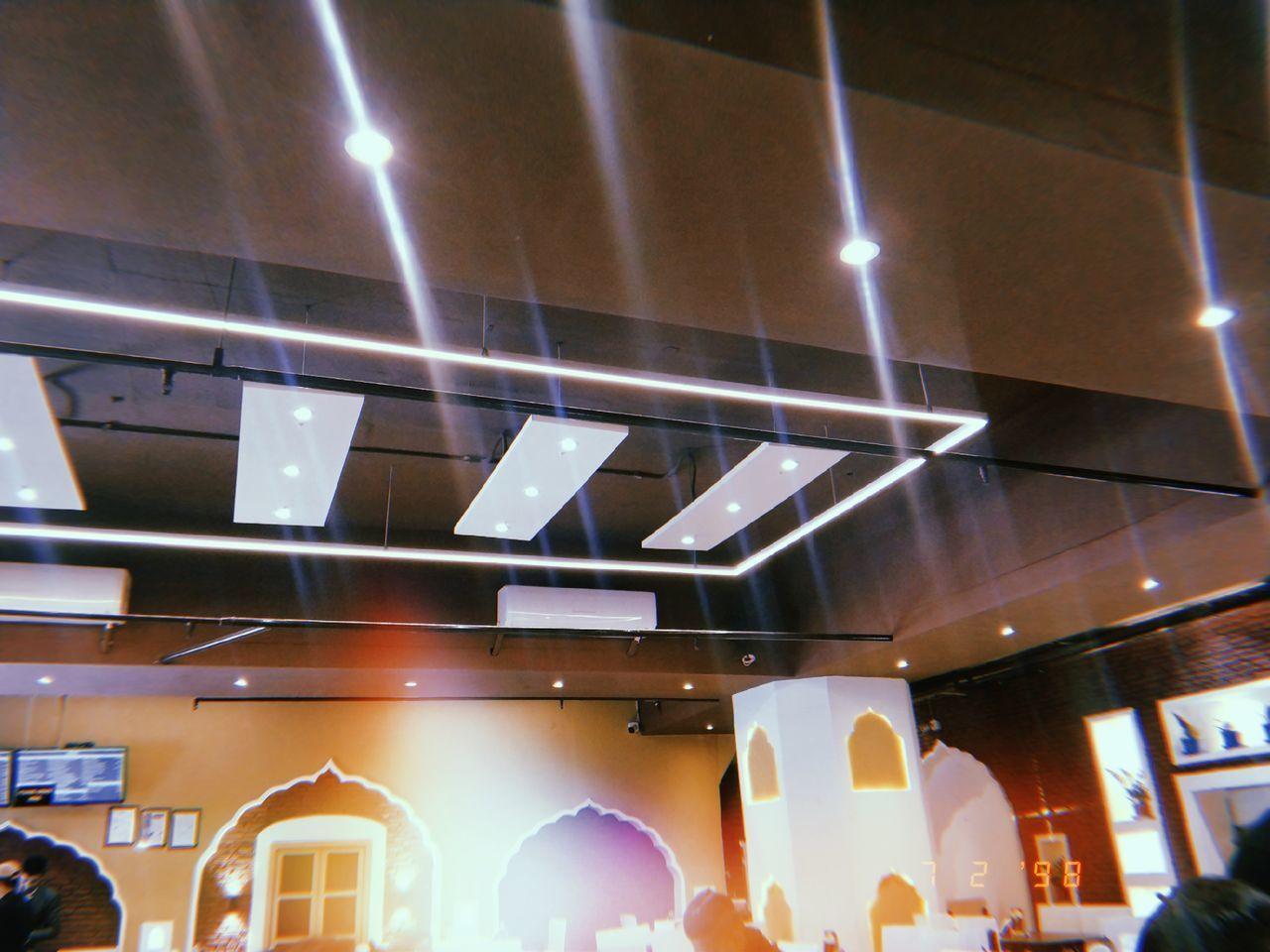 LOW ANGLE VIEW OF ILLUMINATED LIGHTS HANGING AT CEILING