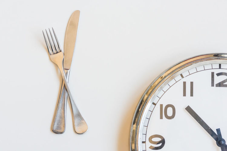 Close-up of clock on table against white background