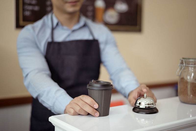 Midsection of man working on table at cafe