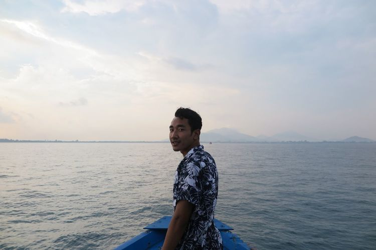 Side view of young man standing in sea against sky
