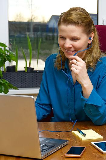 Woman using laptop on desk in office