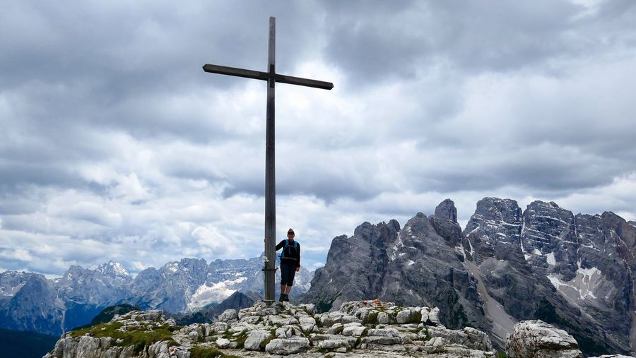 Woman standing by cross on mountain against sky