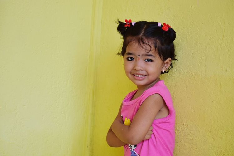 Portrait Of Smiling Girl Standing Against Yellow Wall
