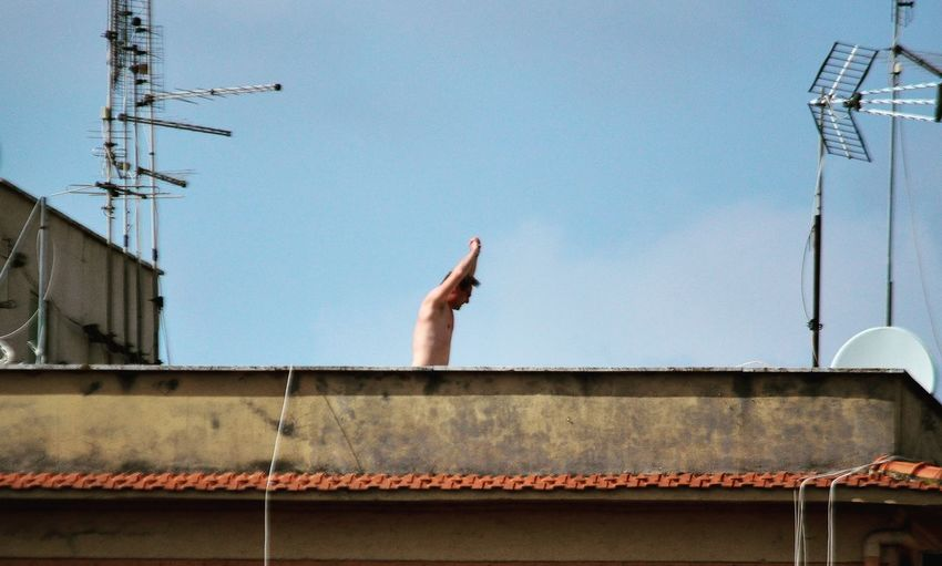 Low angle view of hand against building against clear sky