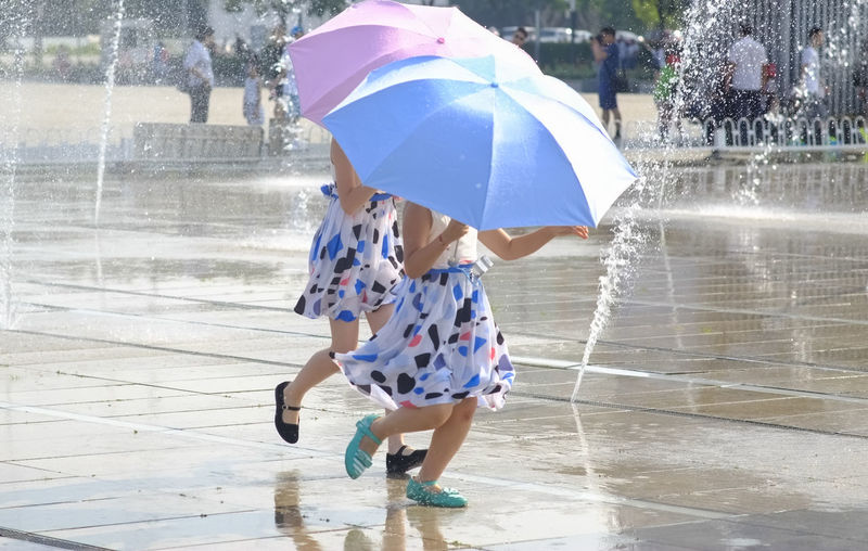 Children playing with umbrellas