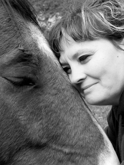 Close-Up Of Woman Leaning On Horse