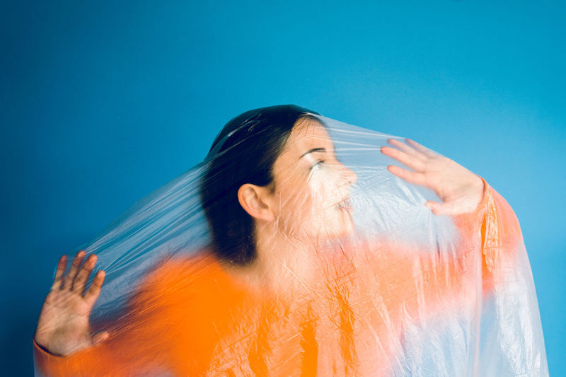 Teenage girl wrapped in plastic against blue background