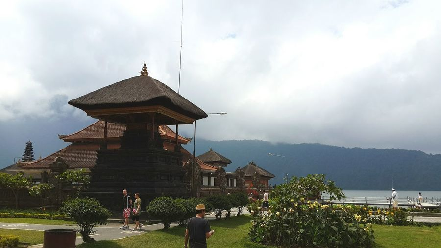 Low angle view of traditional building by lake against cloudy sky
