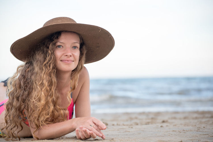 Beach Clothing Front View Hair Hairstyle Happiness Hat Holiday Innocence Land Leisure Activity Long Hair Looking At Camera One Person Outdoors Portrait Sea Smiling Summer Sun Hat Trip Water