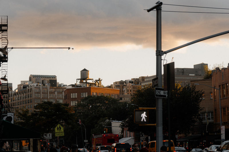 City street and buildings against sky during sunset