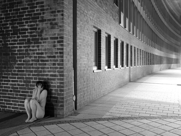 Woman sitting on footpath against brick wall