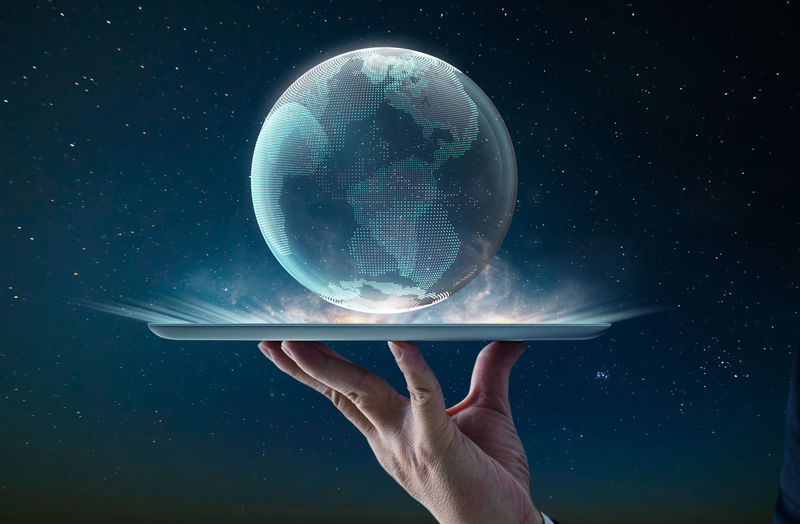 Digital composite image of hand holding carrying planet earth in tray
