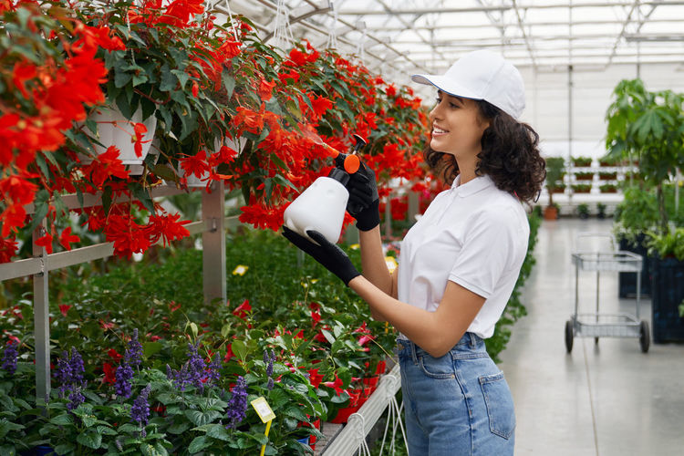 Woman standing by flowering plants