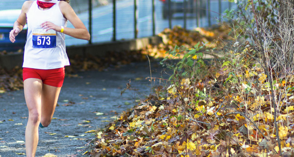 Midsection of woman running outdoors