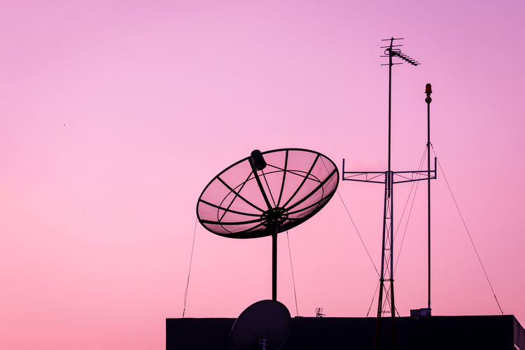 Low angle view of silhouette antenna against clear sky during sunset