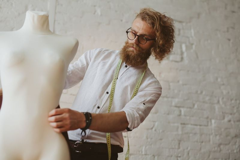 Fashion designer holding mannequin against wall
