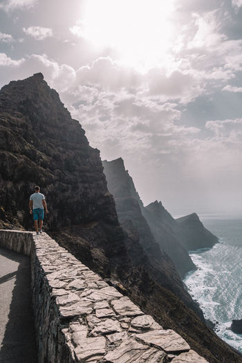 Low angle view of woman standing on cliff by sea against sky