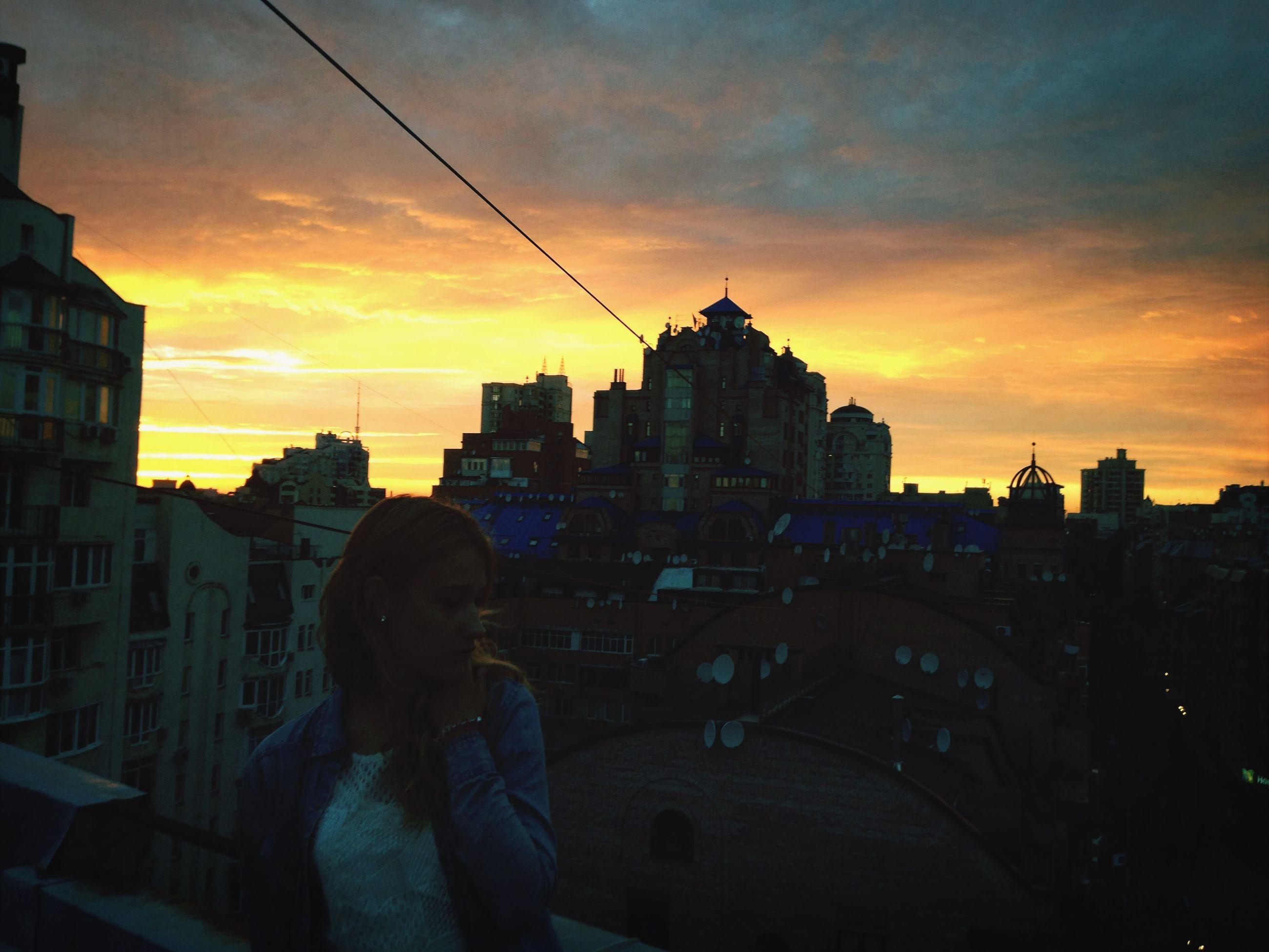 sunset, building exterior, architecture, built structure, orange color, sky, city, silhouette, cloud - sky, cityscape, lifestyles, city life, men, leisure activity, standing, cloud, residential building, building