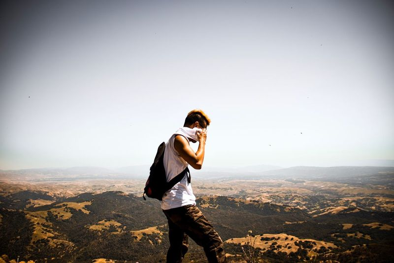 Man standing on landscape against sky