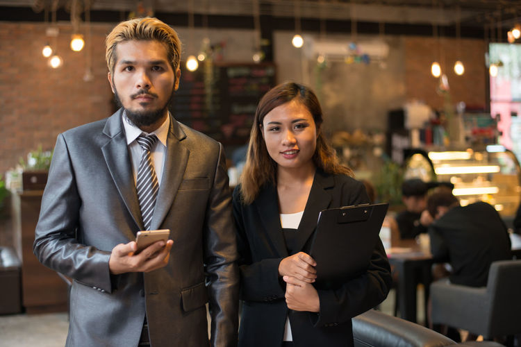 Businesswoman and colleague using mobile phone at cafe