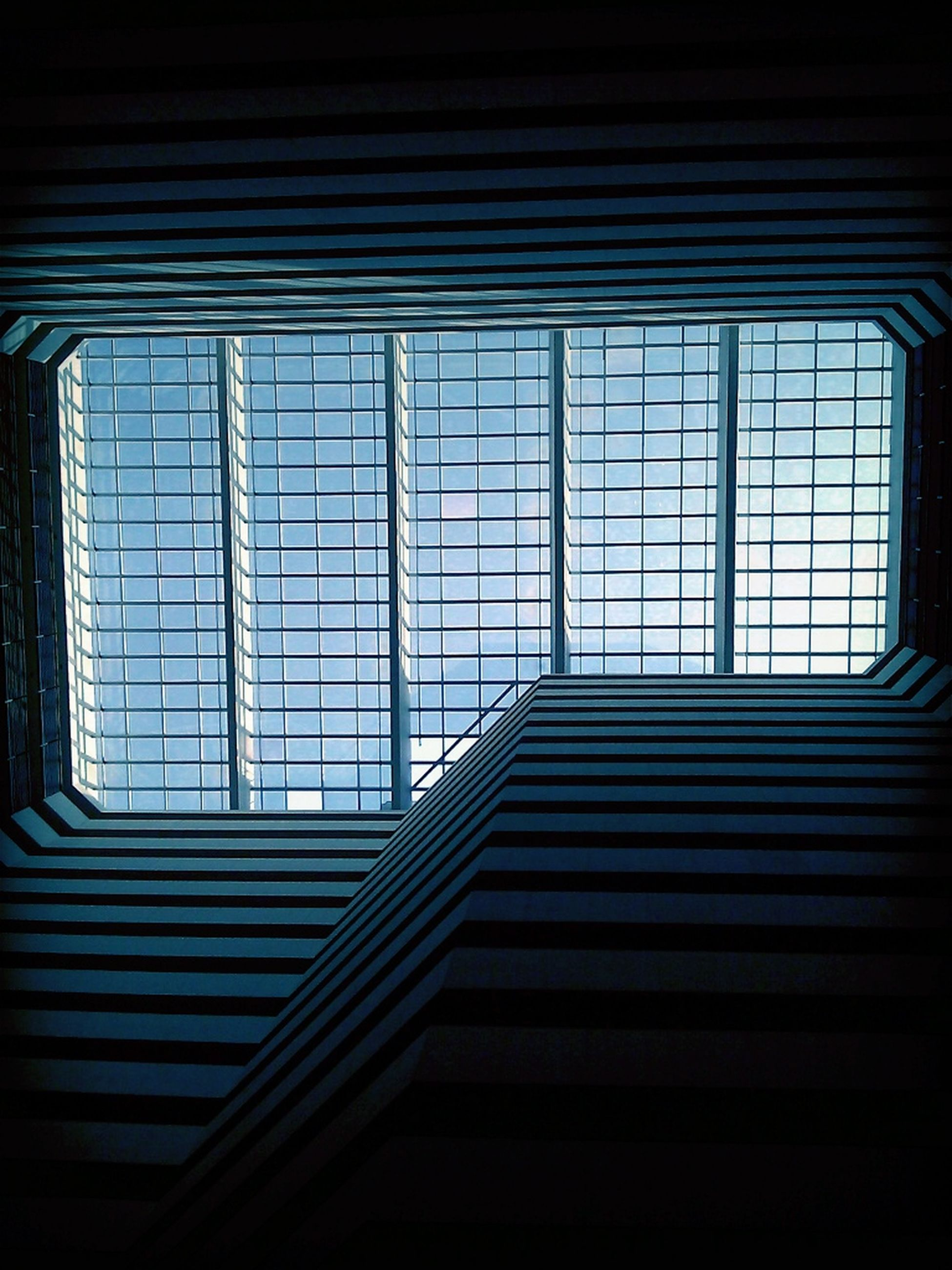 indoors, window, architecture, built structure, low angle view, pattern, building, glass - material, closed, railing, steps, staircase, no people, building exterior, house, dark, sunlight, day, steps and staircases, blinds