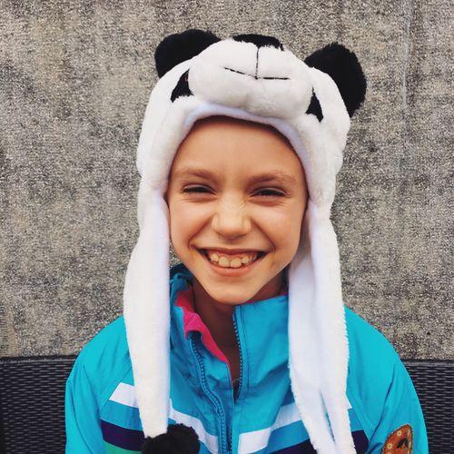 Portrait of smiling boy wearing panda knit hat against wall