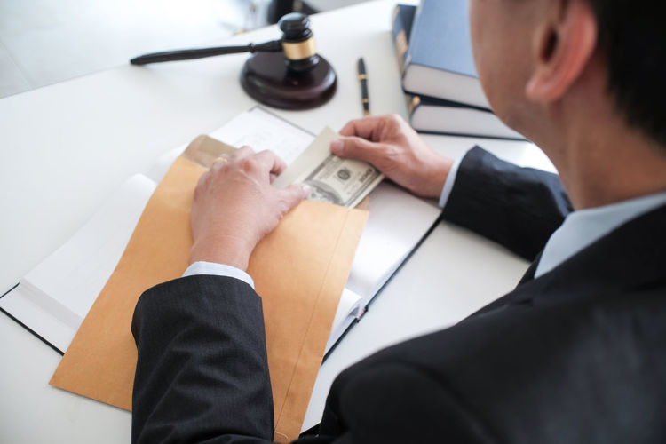 Midsection of businessman holding paper currency in envelop