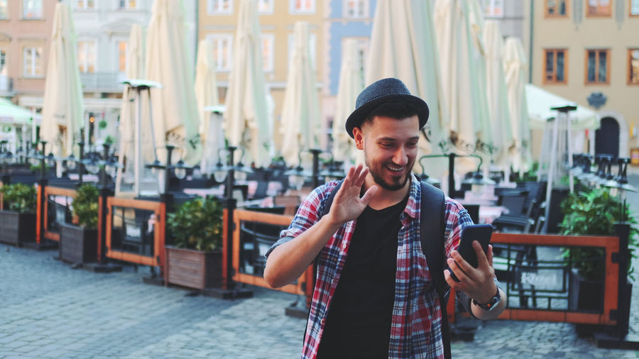 Young man smiling while standing in city