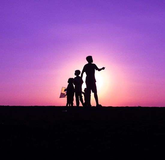 Silhouette children playing on field against sky during sunset