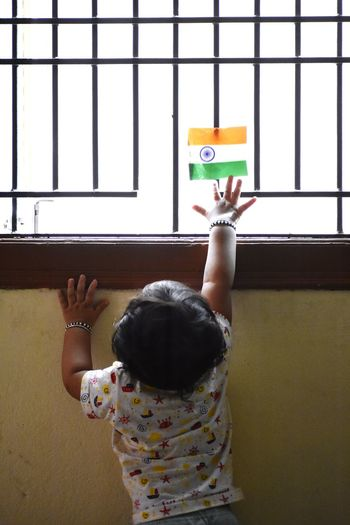 Rear view of baby girl touching indian flag on window