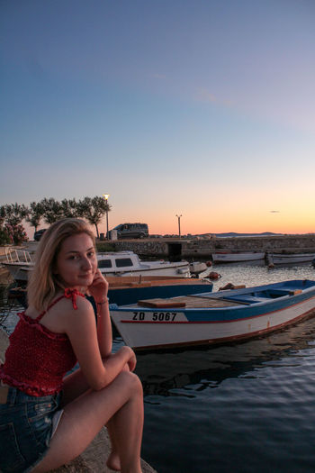 Portrait of young woman in boat against sky during sunset