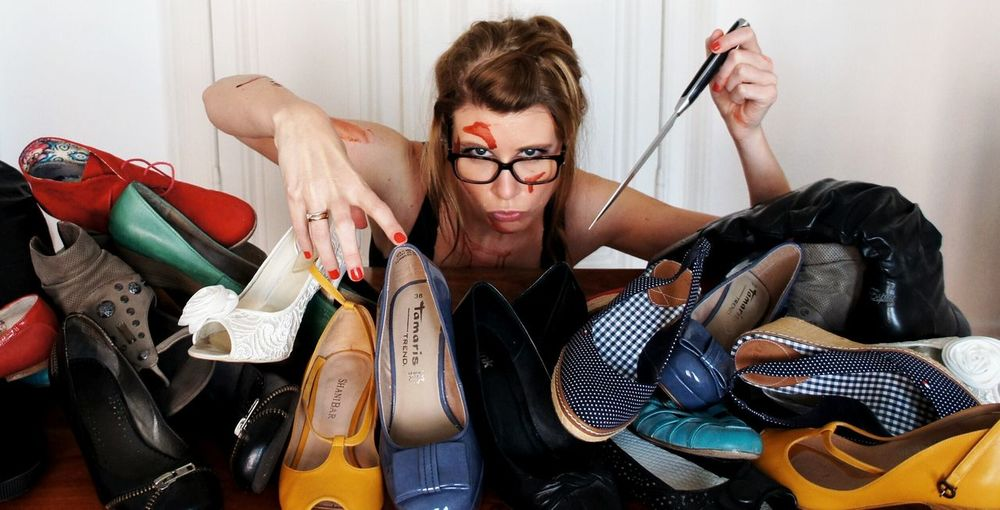 Portrait of young woman pointing knife at heap of shoes