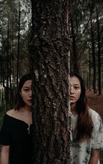 Portrait of beautiful young women peeking by tree trunk in forest