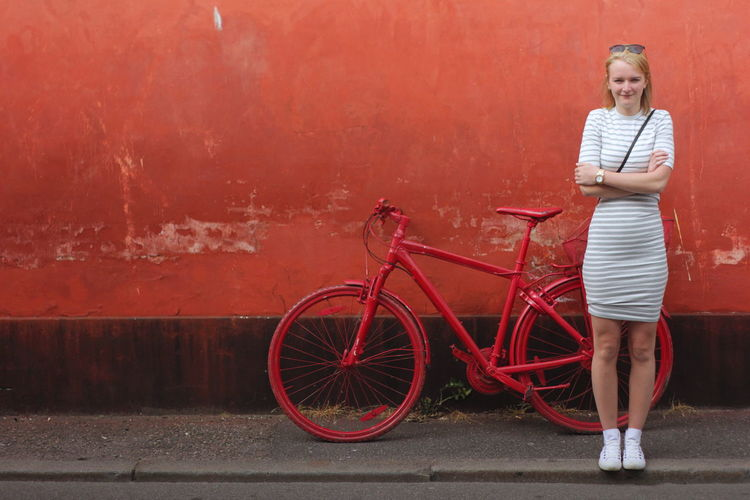 Bicycle Bicycle Port Color Contrast Full Length Girl Girl In Dress Hanging Out Model Outdoors Parked Portrait Posing Red Red Wall Striped Dress Unusual Art Urban White Dress Woman