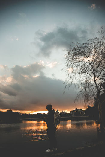 Silhouette person standing by lake against sky during sunset