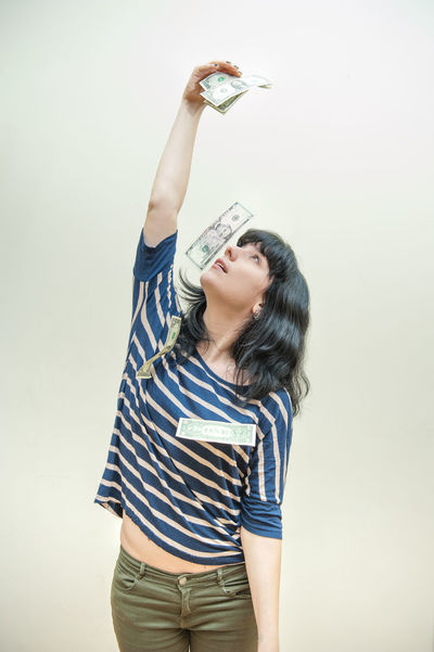 Winner woman takes money from herself Black Hair Casual Clothing Dollars Dreaming Earning Money Lifestyles Long Hair Money Portrait Prize Rich Standing Studio Shot White Background Winner
